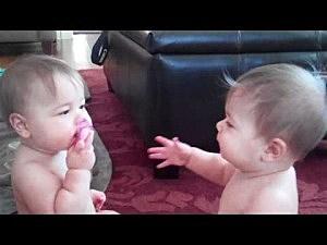 Twin girls play tug o war over pacifier